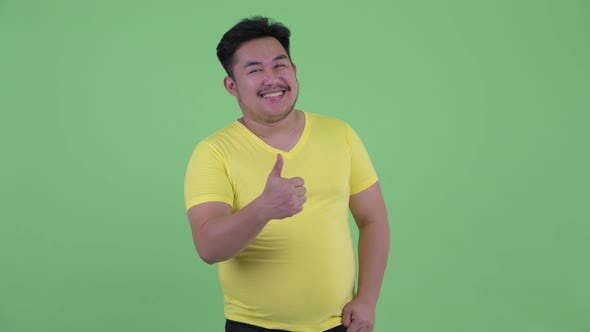 Thumbnail for Happy Young Overweight Asian Man Giving Thumbs Up