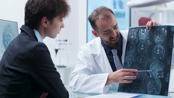 Cover Image for Doctor Showing To a Patient a Detailed X Ray Scan