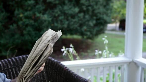 Thumbnail for Senior man reading newspaper and drinking lemonade outdoors