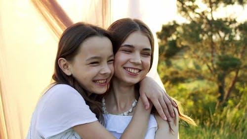 Verspielte Mädchen umarmen sich in der Sommernatur auf dem Land