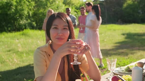 Asian Woman At PArty In Park