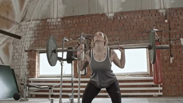 Cover Image for Muscular Woman Doing Barbell Lunges and Squats