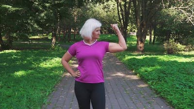 Mature woman in sportswear shows her biceps and muscles, showing her strength and self-confidence.