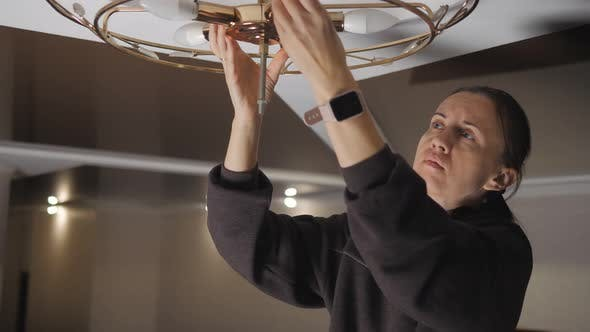 Woman Doing Electrical Maintenance and Replacing the Lamp on the Chandelier