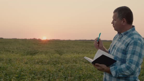 Thumbnail for Germer Makes Notes in a Notebook Stands in a Field