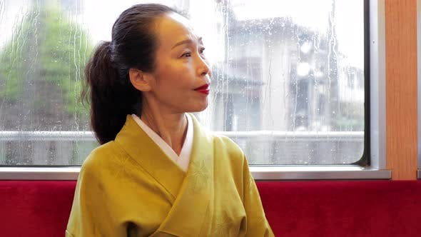Elegant Japanese woman riding a train in Kyoto