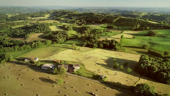 Thumbnail for Aerial view of rolling hills and straw bales in field in Correze, France.