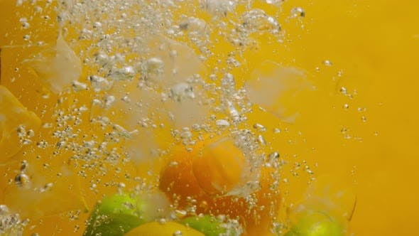 Closeup of Falling Limes Oranges and Lemons Into the Water with Ice on Orange Background Making a