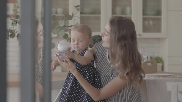 Thumbnail for Beautiful Smiling Young Woman Showing Her Baby Girl How To Drink From the Baby Bottle in the Kitchen