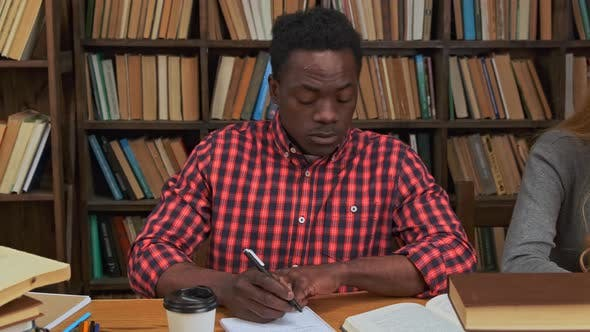 Black Guy Surrounded By Books in Library