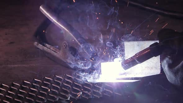 Thumbnail for Close view of arc welder sparking as sparks shoot around.