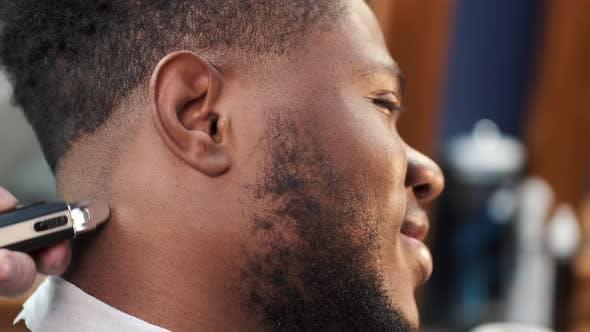 Young Africanamerican Man Visiting Barbershop for Haircut