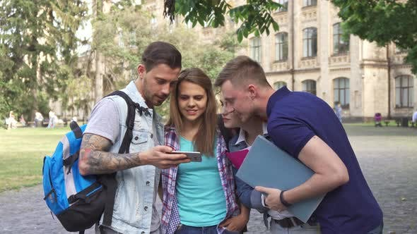 Thumbnail for Four Students Look at Smartphone Screen on Campus