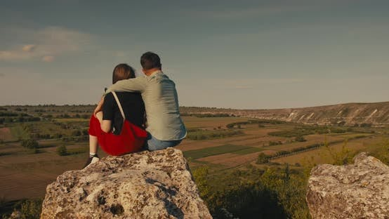 Cover Image for Young Couple Hugging While Sitting on A Cliff with A Beautiful View