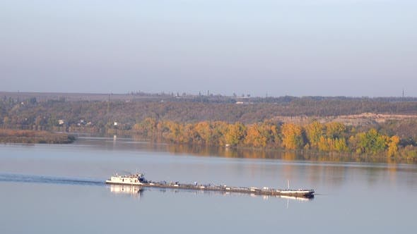 Thumbnail for Cargo Ship Floating Along River. Colorful Trees on Shore, Landscape