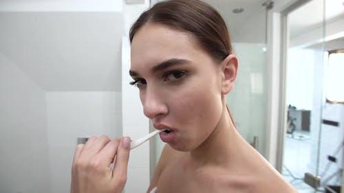 Teeth Hygiene. Woman Brushing Teeth And Looking At Camera