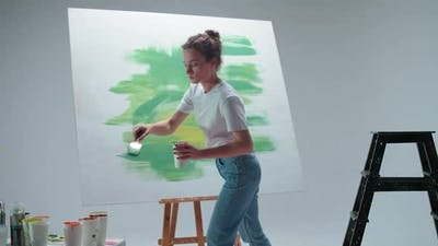 Female Artist Draws with a Brush on a Large Canvas in a White Room a Talented Artist Draws a Color