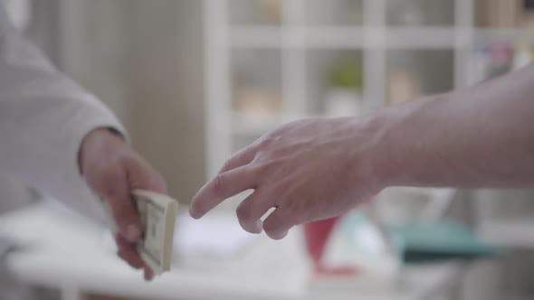 Thumbnail for Close-up Hands of the Patient Giving Money To Doctor. The Doctor Takes a Bribe From a Patient and