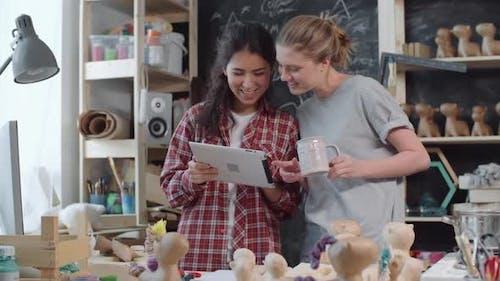 Artsy Women in Workshop Looking at Tablet
