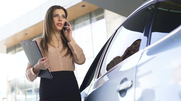 Thumbnail for Busy Female District Attorney Talking With Someone on Smartphone Near Vehicle
