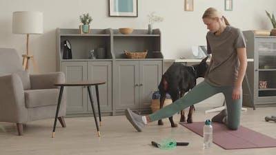 Sportswoman Training Doberman at Home