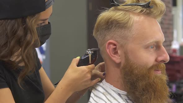 Close up of professional young barber girl in mask doing haircut for her client.
