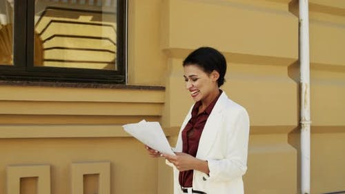 Cheerful Businesswoman Reading Docs Outside