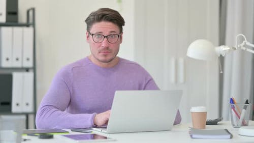 Middle Aged Man with Laptop Shaking Head, No