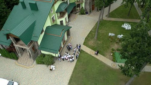 Many people are standing near houses with green tiled roofs in the middle of the forest