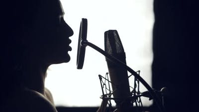 Silhouette of beautiful woman is singing a song in front of a microphone