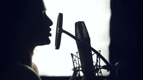 Silhouette d'une belle femme chante une chanson devant un micro