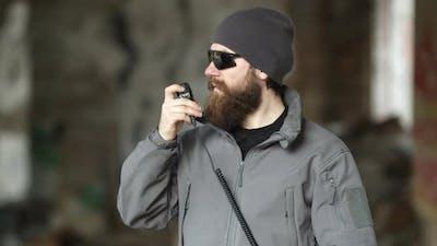 Seriouslooking Bearded Man in Sunglasses Using Walkie Talkie