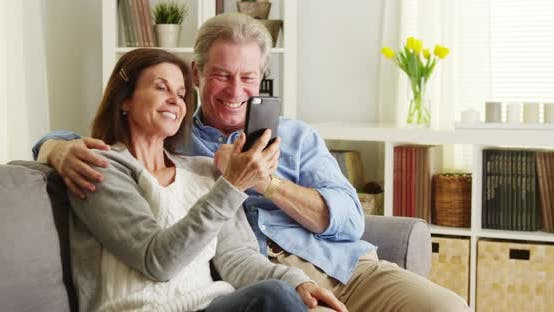 Thumbnail for Senior couple using smartphone on couch