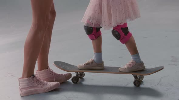 Unrecognizable Woman Teaching Daughter Skateboarding