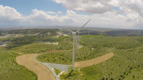 Huge Wind Turbines Rotating Under Cloudy Sky, Sunny Weather Changing to Rainy