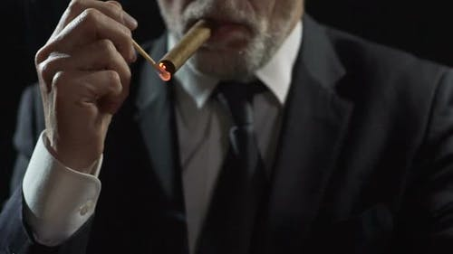 Millionaire Lighting Expensive Havana Cigar With a Match, Power and Authority