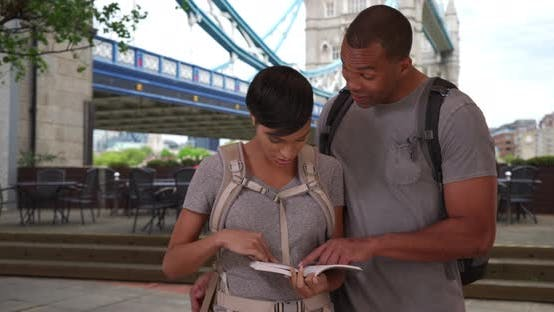 Thumbnail for Vacationing black couple looking at guide book  for places to visit in London