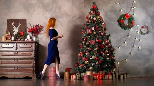Beautiful Woman in Blue Dress Decorates Christmas Tree with New Year Toys