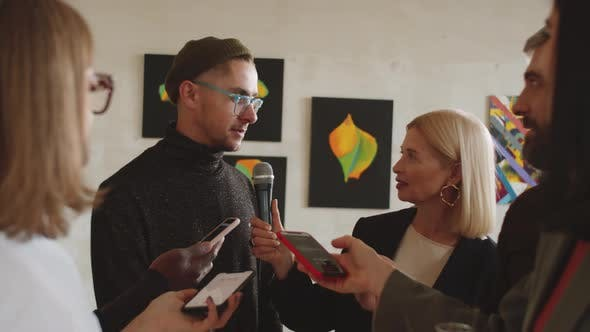 Male Artist Giving Interview to Press in Gallery