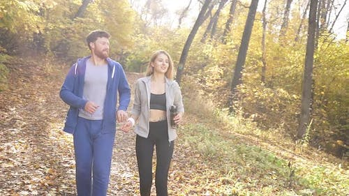 Athletic Young Couple Dressed in Sportswear, Relaxing Jogging in a Park in the Fresh Air, Autumn
