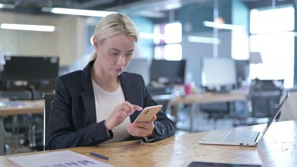 Thumbnail for Serious Businesswoman Using Smartphone at Work
