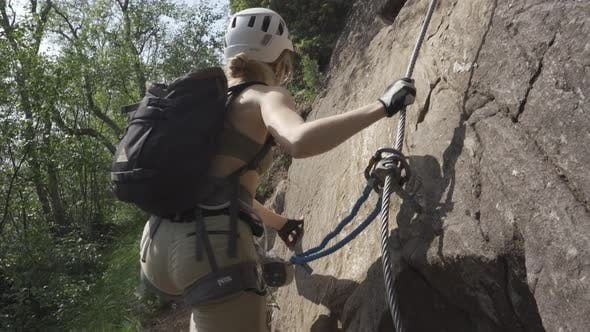 Rock Climber Attaching Rope To Guideline And Climbing Cliff