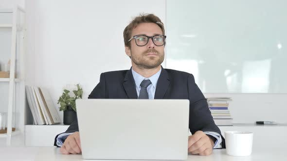 Thinking and Smiling Businessman Sitting in Office
