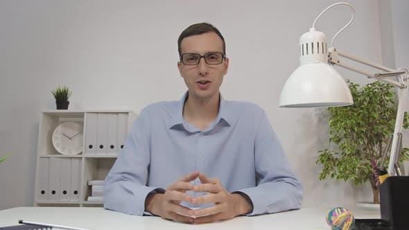 Businessman in Office Speaks Via Video Link