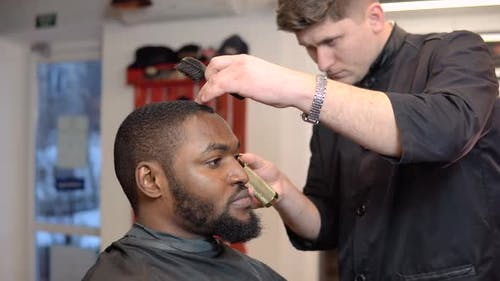 Young Male Hairdresser Cuts Young Man in Barbershop