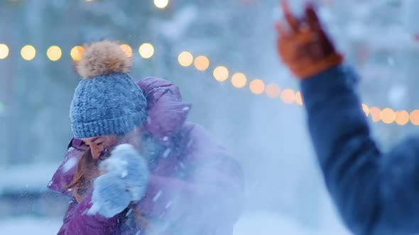 Thumbnail for Girl in Warm Jacket and Hat Throws Snow with Happy Boyfriend