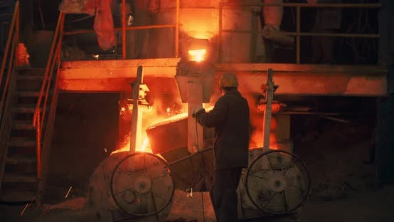 Thumbnail for Foundry, a man pours molten metal into the mold