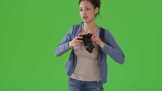 A Latina woman takes pictures on green screen