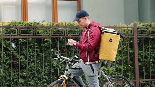 A Delivery Man with a Thermal Backpack Uses a Mobile Phone