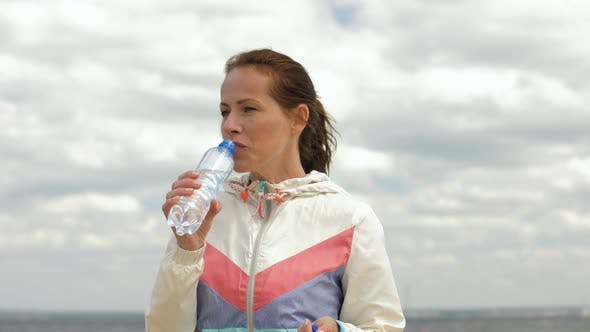Thumbnail for Woman Drinking Water After Exercising on Beach